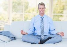 Man Meditating on couch by window. Digital composite of Man Meditating on couch by window Stock Image