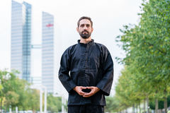 Man meditating doing martial arts in city Stock Photo