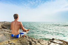 Man meditating in front of sea Stock Image