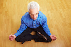 Man meditating in living room Stock Photos