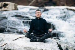 Man meditating in Lotus Pose on waterfall Stock Image