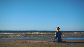 Man in Lotus pose meditating at the beach stock footage