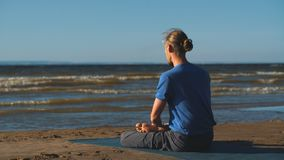 Man in Lotus pose meditating at the beach stock video footage