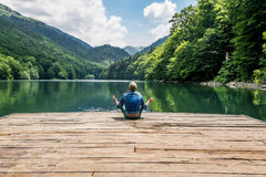 The man meditating in lotus position on Biogradsko lake in the n Royalty Free Stock Photography