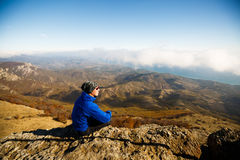 Man meditating on a mountain peak rock. Hiker enjoy the scenery above clouds on summit Stock Photos