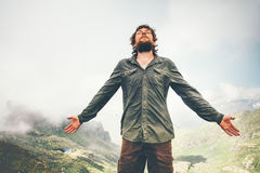 Man meditating in mountains getting energy hand raised. Travel Lifestyle concept adventure summer vacations outdoor hiking mountaineering bearded wayfarer Stock Photo