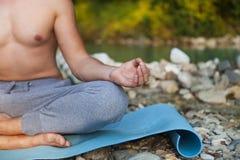 Man meditating near the mountain river. Yoga practicing outdoors Stock Photos
