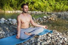 Man meditating near the mountain river. Yoga practicing outdoors Stock Photo
