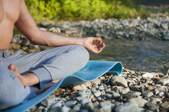 Man meditating near the mountain river. Yoga practicing outdoors Royalty Free Stock Image