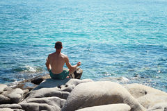 Man Meditating Near The Sea sitting on a rock and Doing Yoga On the Beach in a lotus position Royalty Free Stock Photo