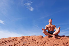 Man meditating outdoors Stock Images