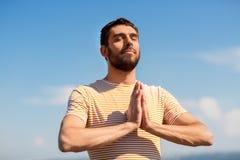 Man meditating outdoors over sky Stock Photography