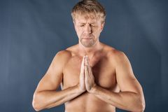 Man meditating. Peaceful calm fit guy practicing yoga in lotus pose, freedom and calmness concept, close up view royalty free stock photos