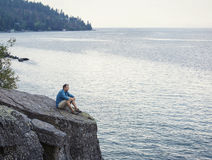 Man meditating and praying on cliff edge overlooking ocean Royalty Free Stock Photography