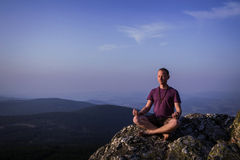 Man meditating on a rock Stock Photo