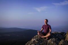 Man meditating on a rock Stock Photo