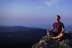 Man meditating on a rock Stock Photos