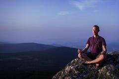Man meditating on a rock Stock Photos