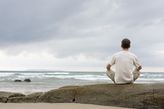 Man meditating on a rock at the sea Stock Image