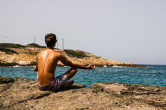 Man Meditating on the Rock Shore Stock Photo