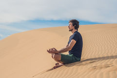 A man is meditating on the sand in the desert stock image