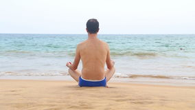 Man meditating on sandy beach in the tropics stock video footage