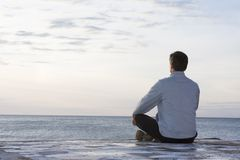 Man meditating at the sea royalty free stock image