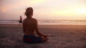 Man meditating at sunset stock video