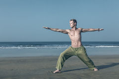 Man meditating in warrior pose. Young man doing yoga and meditating in warrior pose at sea beach Stock Images