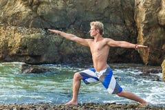 Man meditating in warrior pose Royalty Free Stock Images