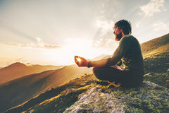 Man meditating yoga lotus pose at sunset mountains. Travel Lifestyle relaxation emotional concept summer vacations outdoor harmony with nature calm scene Royalty Free Stock Images