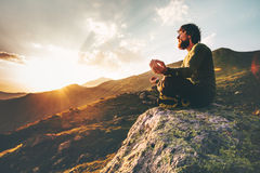 Man meditating yoga lotus pose at sunset mountains. Travel Lifestyle relaxation emotional concept summer vacations outdoor harmony with nature Royalty Free Stock Image
