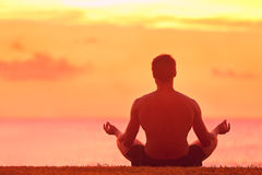 Man Meditating In Yoga Lotus Position at Sunset. Meditation and Yoga. Rear view of young man meditating in lotus position. Male is practicing yoga at beach. He Royalty Free Stock Photography
