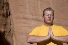 Man in meditation close up. A man in a yellow shirt meditating Royalty Free Stock Images