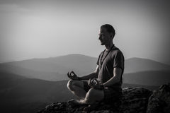 Man meditation on a rock Stock Images