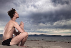 Man in the meditation on the shore of the sea Stock Photo