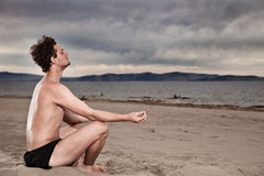 Man in the meditation on the shore of the sea Royalty Free Stock Photography