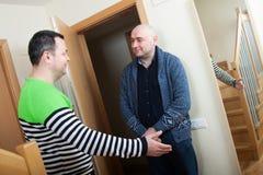 Man meeting another man at door. Adult men opening door his neighbor royalty free stock photography
