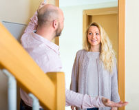 Man meets his female guest. Adult men meeting his female guest near door and smiling Stock Photography