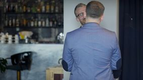 A man meets his guest in a restaurant and invites to a table. A slender businessman in stylish glasses and in a business suit happily hugs his colleague by the stock video