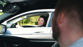 A man meets a woman in traffic. A man meets a woman on the road stock footage