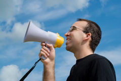 Man With Megaphone. A low angle view of a man talking into a megaphone with the sky behind him Stock Images