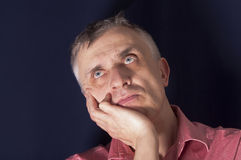 Man in Melancholy. Studio portrait of a man in melancholy, looking up and holding his head royalty free stock photography