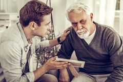 Adult son showing to his old father a family photo. stock photography