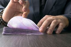 Man in Men's Suits.Bribe and corruption with euro banknotes. Rich man in Men's Suits with bracelets, pen in table. Bribe and corruption with euro banknotes royalty free stock photo