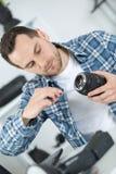 Man mending camera lens. Man mending the camera lens Stock Photography