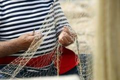 Man Mending Nets. An old fisherman sits, mending his fishing net Stock Photo