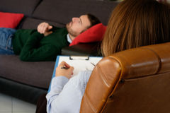 Man with mental health problem in the psychiatrist studio. Coach stock image