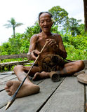 Man Mentawai tribe prepares poison for the arrows for hunting. stock images