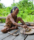 Man Mentawai tribe prepares poison for the arrows for hunting. stock photo